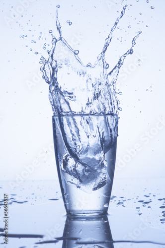 Splash of water in glass with drops on light background