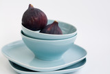 Ripe figs lying on a blue plate on a white background