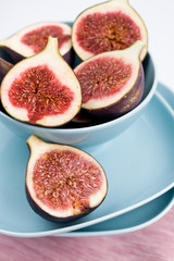 Ripe figs lying on a blue plate on a pink napkin