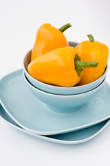 Three yellow sweet peppers are on blue plates