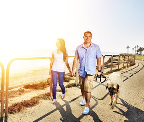 couple walking pet dog by the ocean