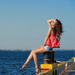 Pretty smiling girl sitting at the old berth in summer day