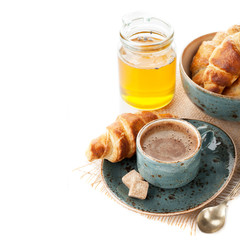 Coffee, croissants and honey for a delicious breakfast