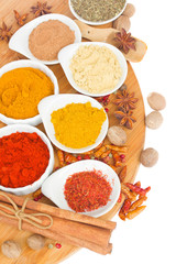 colorful plates of  spices on wooden board