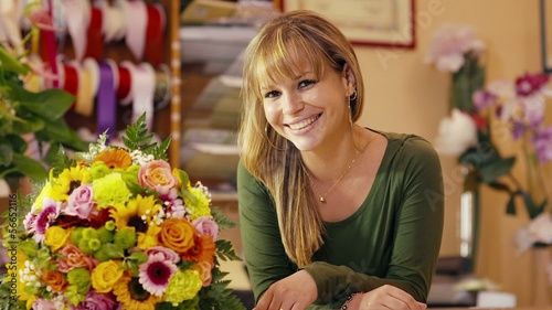happy woman working as florist in flower shop