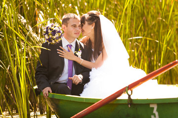 Bride and groom hugging in boat on the lake