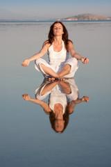 Young woman making yoga at sea