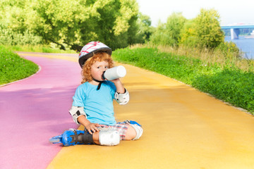 Boy rollerblading and drink water from bottle
