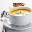 Pumpkin cream-soup in white bowl with silver spoon
