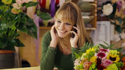 florist talking with customer on telephone and selling flowers