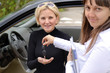 Happy saleswoman handing over car keys