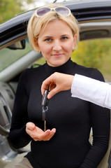 Woman receiving the keys to her new car
