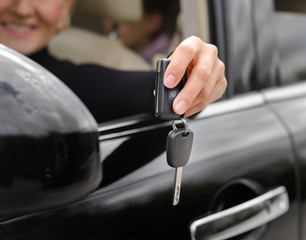 Woman driver holding out her car keys