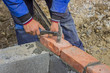 Man laying concrete block and bricks wall