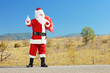 Full length portrait of a santa claus with bag hitchiking