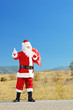 Santa claus with bag on an open road hitchiking