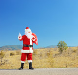 Full length portrait of a santa claus with bag on a road