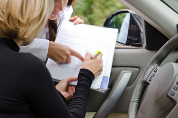 Two woman signing a deal to purchase a car