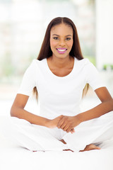 young african american woman sitting on bed