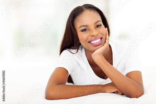 young african woman lying on bed