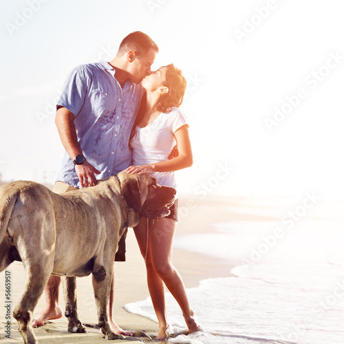 couple on the beach with dog kissing