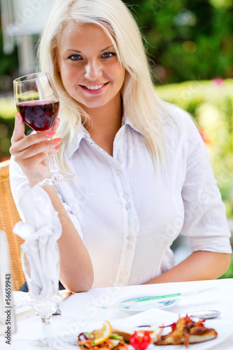 Young happy woman with glass of redwine