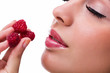 young beautiful  woman eating raspberries
