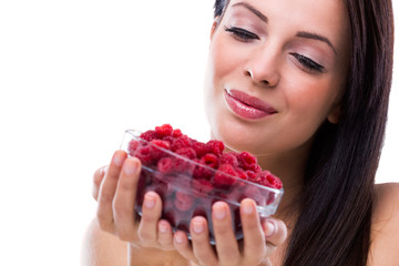 Close up of smiling woman holding raspberries