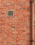 Brown Brick Wall with Vent and Old Pipe