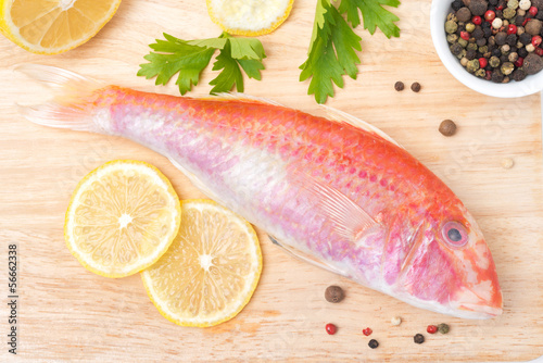 fresh surmullet, lemon and spices on a wooden board