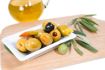 stuffed olives  with olive oil and branch of an olive tree on a