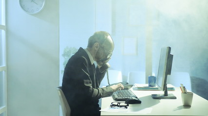 Businessman wearing a gas mask working in his office