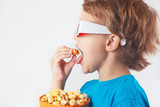 Little boy in 3D glasses eating popcorn