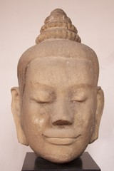 head of smiling buddha made by stone