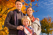 Family in front of colorful trees in autumn or