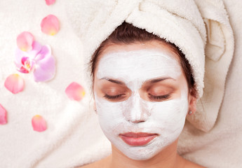 Young woman with clay facial mask in beauty salon.