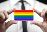 Businessman holding a business card with a Rainbow Flag