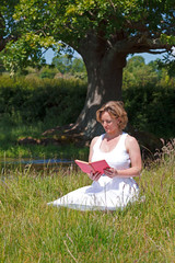 Woman sat in a meadow reading a book