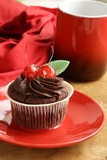 Chocolate Cupcake with cherries and cream on a red plate