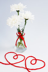 White flowers in a small glass vase and two hearts from threads