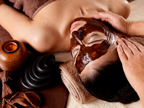 Spa massage for woman with facial mask on face