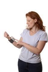 Hübsche rothaarige Frau mit Blutdruckmessgerät
