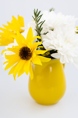 Yellow jug with yellow and white flowers on a light background