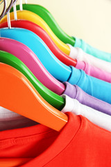 Different shirts on colorful hangers on beige background