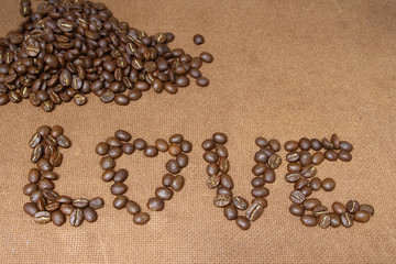 Love alphabet by coffee beans on wood board