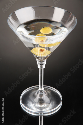 Martini with green olives on grey background