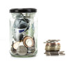 Glass jar with coins and notes from around the world on a white