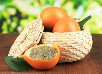 Passion fruits in wicker basket on table on bright background