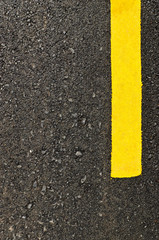 Closeup new asphalt road with yellow line
