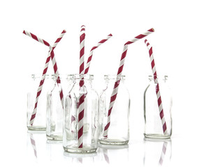 Six empty bottles of milk with drinking straws in a line on a wh